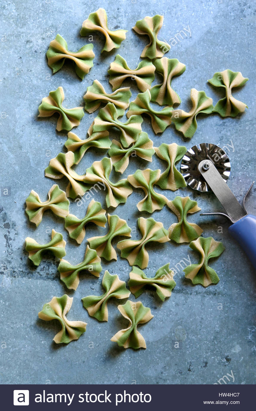 Fresh Striped spinach farfalle pasta on metal background.Top view - Stock Image