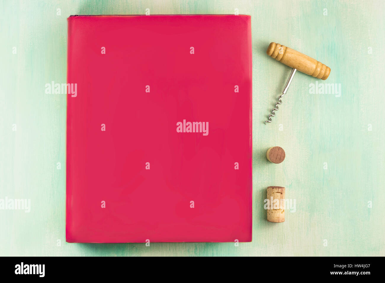 Vibrant pink book, corkscrew, and wine corks - Stock Image