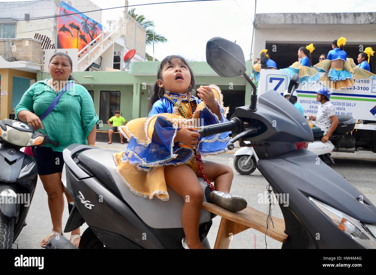 little girl carnival goer sits on scooter moped eating crisps chips isla mujeres - Stock Image