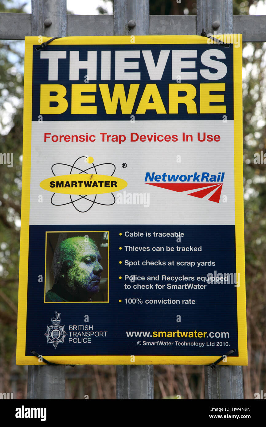 A warning sign to thieves that smartwater forensic trap devices are in place next to the West Coast Main Line railway - Stock Image