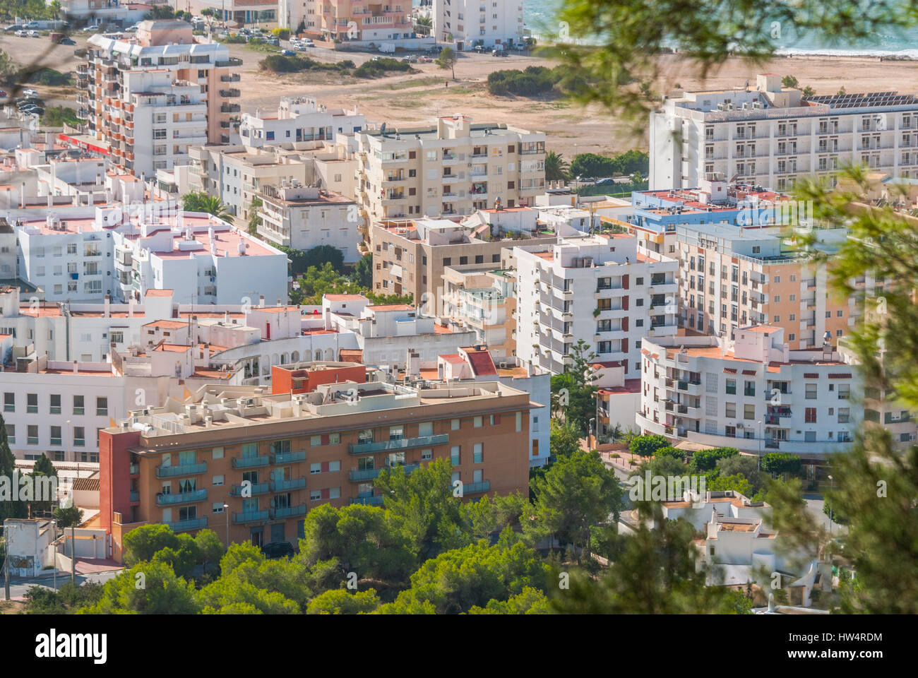 View through naturally framing trees, from hillside of nearby town: San Antonio Sant Antoni de Portmany in the Balearic - Stock Image