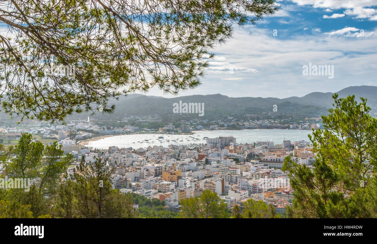 View through naturally framing trees, from hillside of nearby town: San Antonio Sant Antoni de Portmany in Ibiza. - Stock Image