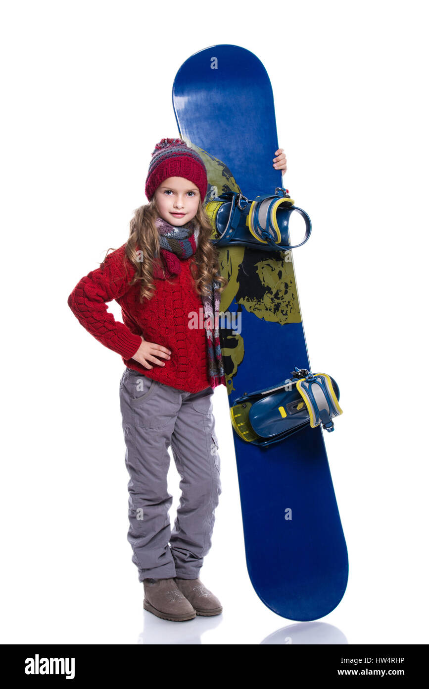 Smiling little girl with curly hairstyle wearing knitted sweater, scarf, hat and gloves with blue snowboard, isolated - Stock Image