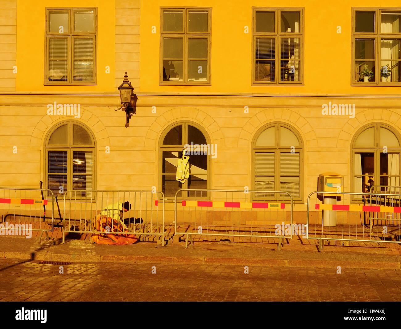 Workman in street bathed in dawn sunlight, Riddarholmen, Stockholm, Sweden, Scandinavia - Stock Image