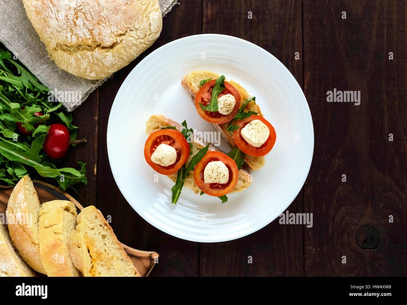 Bruschetta with arugula, tomatoes, mozzarella, olive oil on slices of chiabatta. Light breakfast. The top view - Stock Image