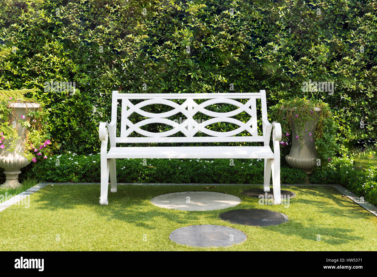 White Wood Bench Chair With Bush Background In Garden At Home Stock