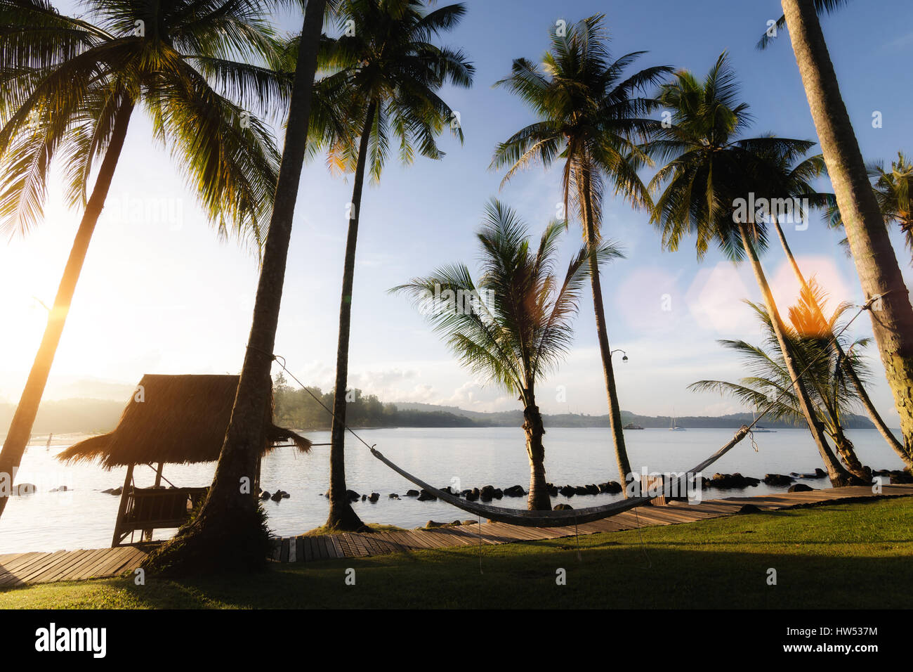 View of tropical beach with coconut palm trees,hut and cradle at Phuket, Thailand. Summer, Travel, Vacation and Stock Photo