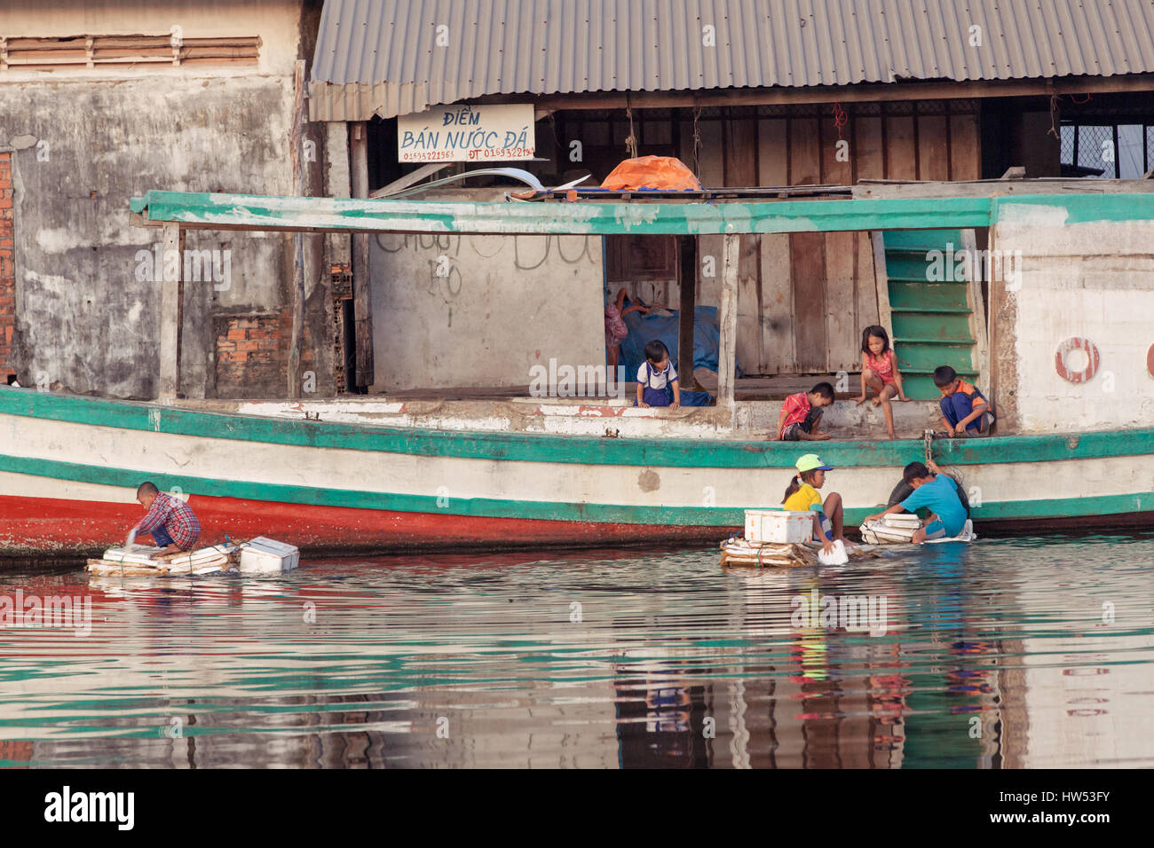 Phu Quoc, Vietnam - April 7, 2014: Children play in the dirty water near the fishing village on April 7, 2014, Phu - Stock Image