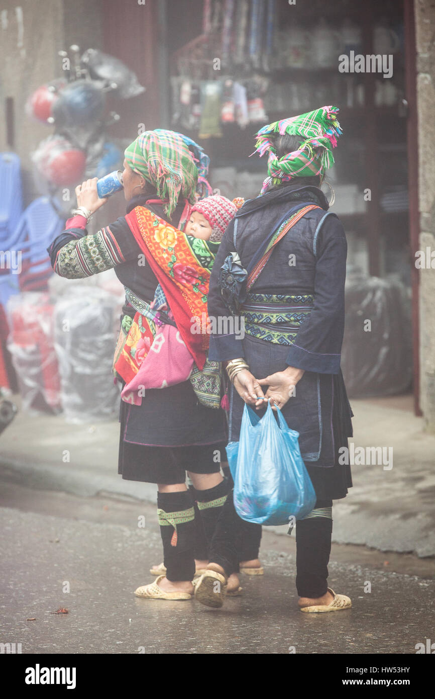 Sapa, Vietnam - May 6, 2014: Hmong women in traditional clothes with modern soda at the local market in Sapa village, - Stock Image