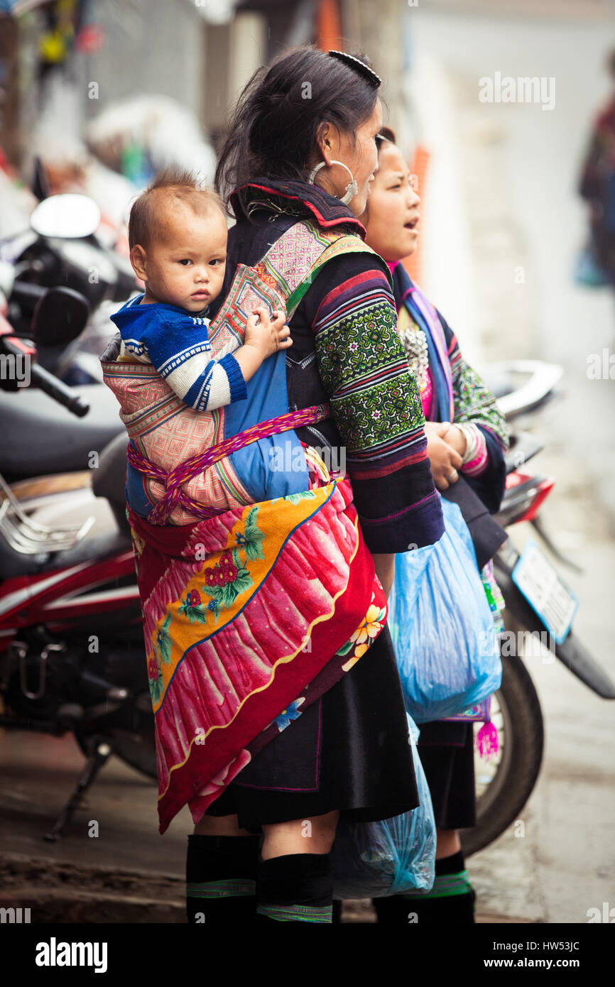 Sapa, Lao Cai, Vietnam - 6 May 2014: Ttribal Hmong woman with baby on the street of Sapa, Northern Vietnam. - Stock Image