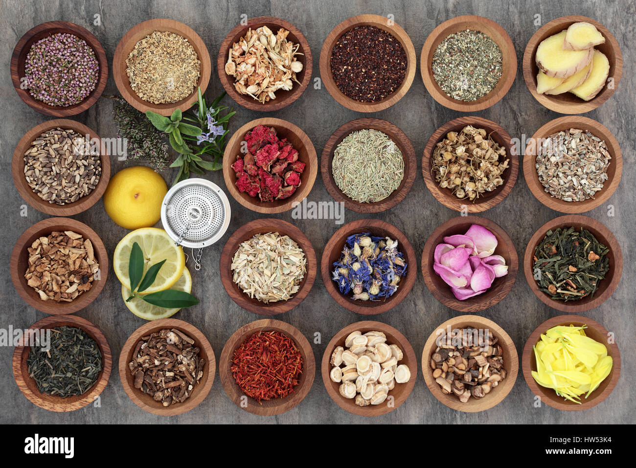 Healthy herb tea selection in wooden bowls and loose with strainer, teas also used in alternative medicine. - Stock Image