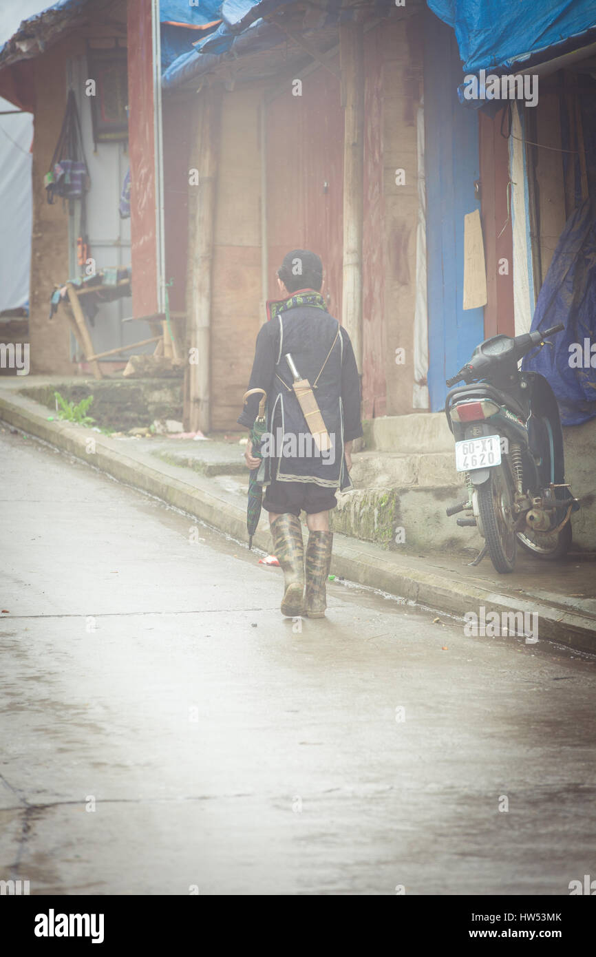Sapa, Vietnam - May 6, 2014: Hmong man in traditional clothes walking down the street in the heavy fog in Sapa village, - Stock Image