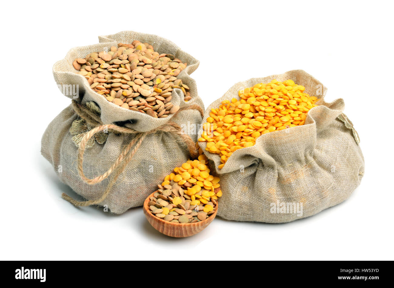 green and yellow lentils in the sacks and spoon wooden isolated on white background - Stock Image