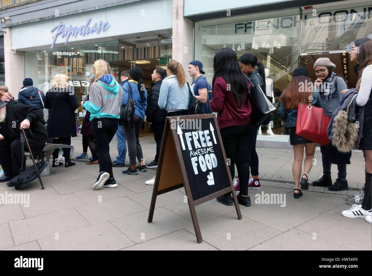People queue for free food in Deliveroo promotion in North London shopping centre - Stock Image