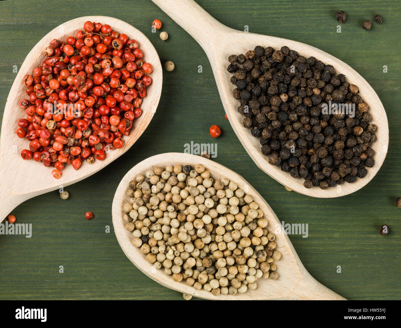 Whole Red White and Black Pepper Corns Against a Green Background - Stock Image