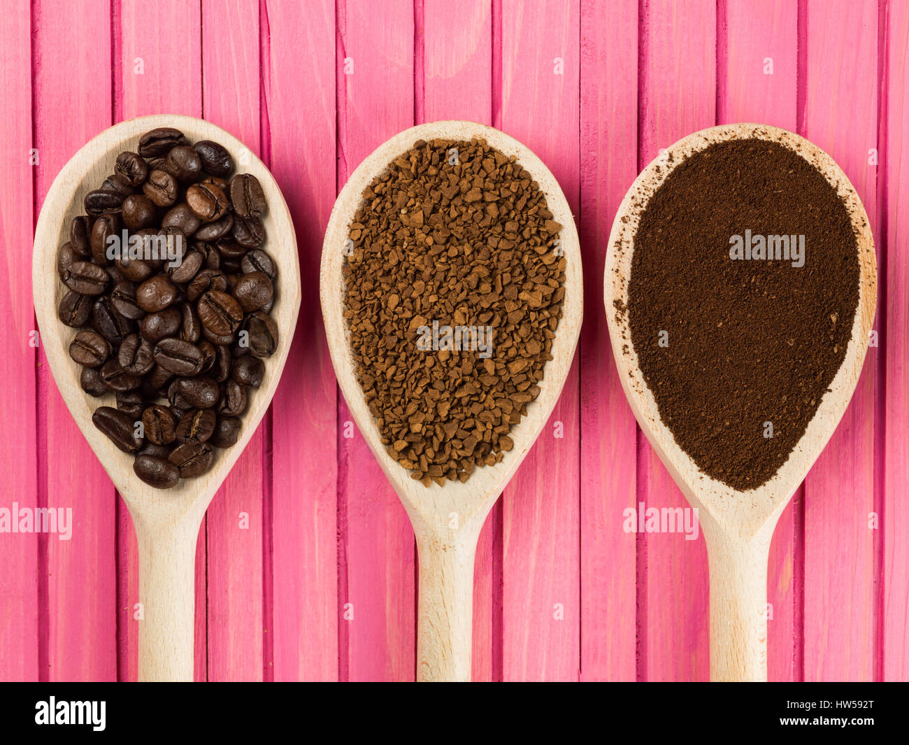 Spoonfuls of Instant Granulated and Roast Coffee Beans Against a Pink Background - Stock Image