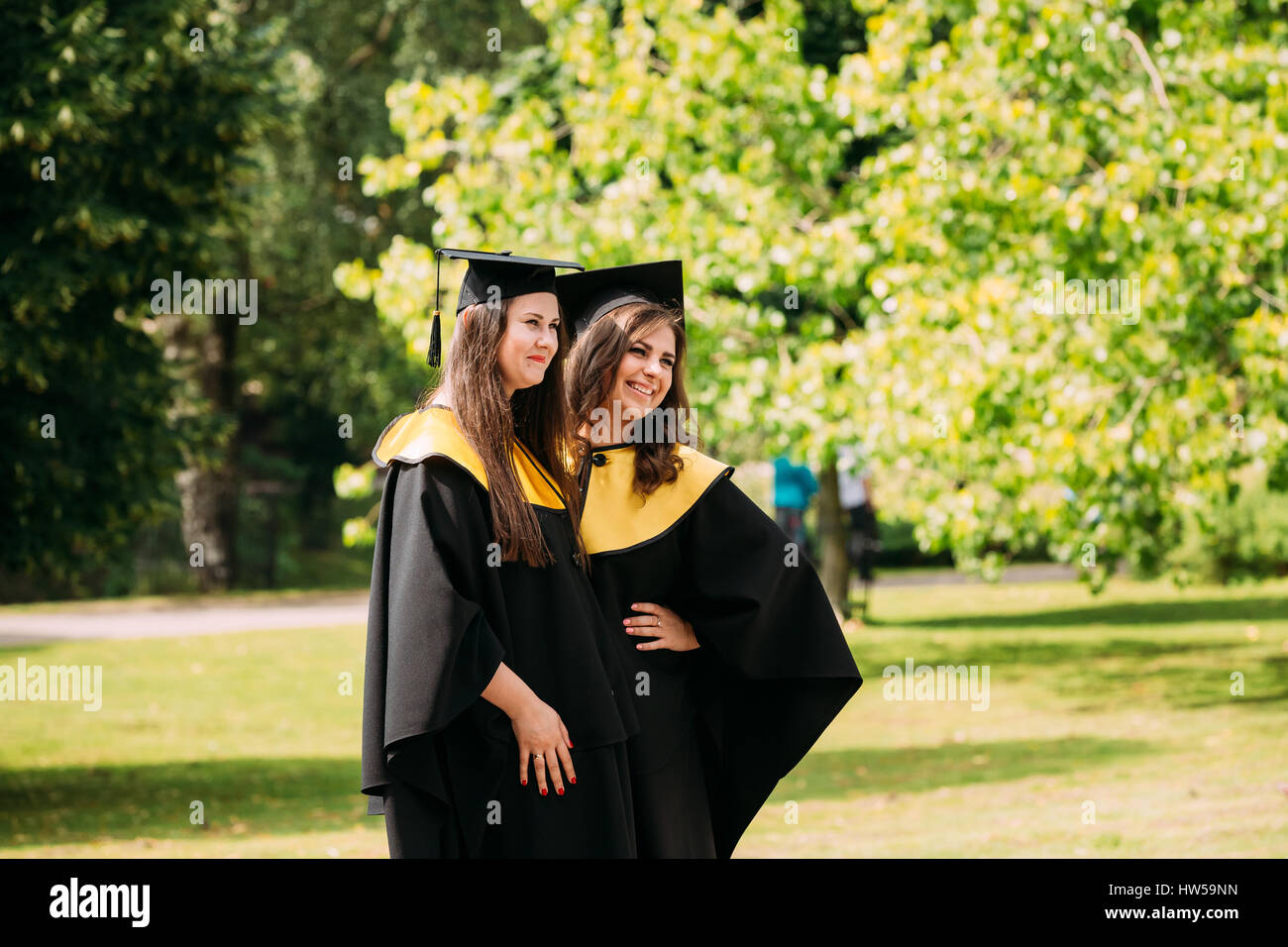 Riga, Latvia - July 1, 2016: Two young women graduates of the University of Latvia dressed in gown graduates and - Stock Image