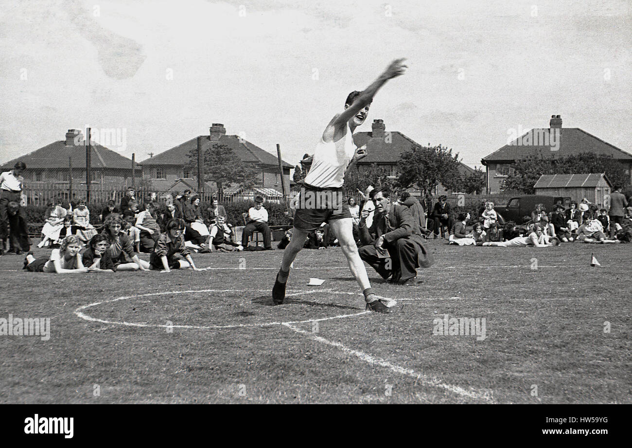 1940s, schoolboy throws the discus at a school sports day, England. - Stock Image