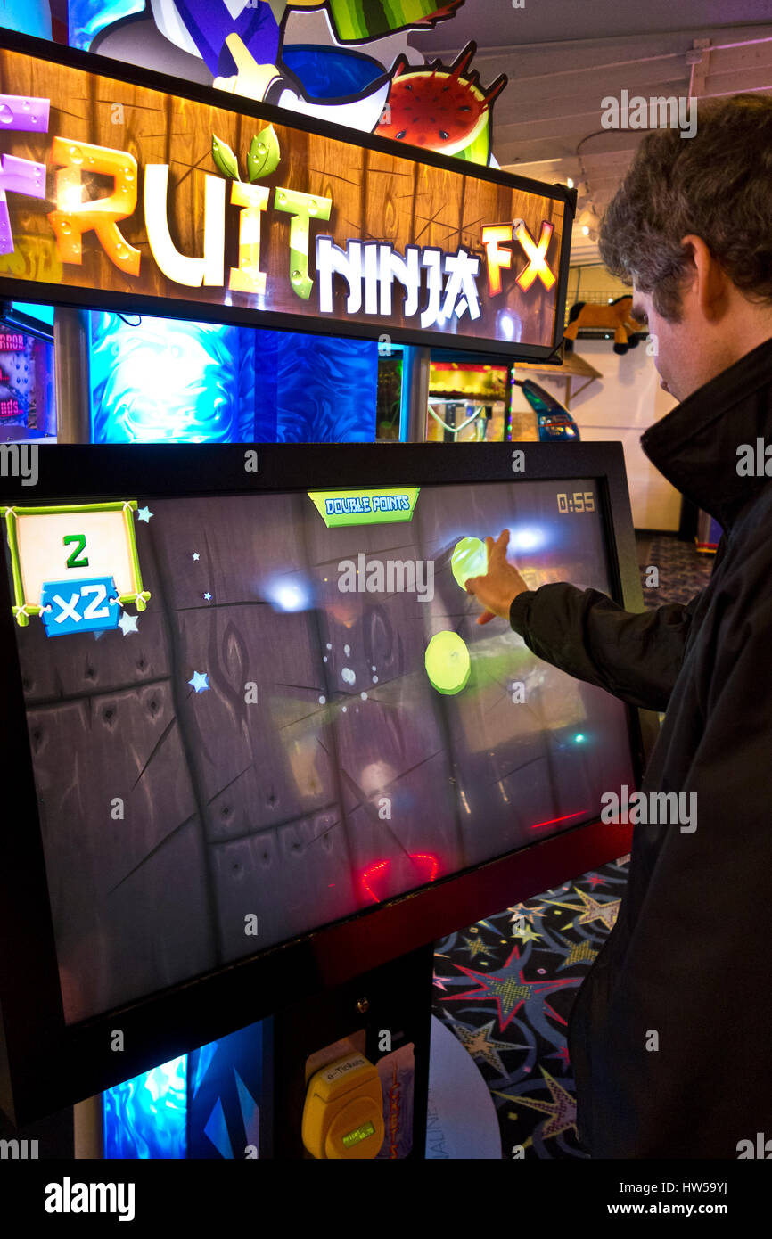 Man swiping the screen while playing Fruit Ninja FX game in a video arcade in Long Beach, Washington. - Stock Image