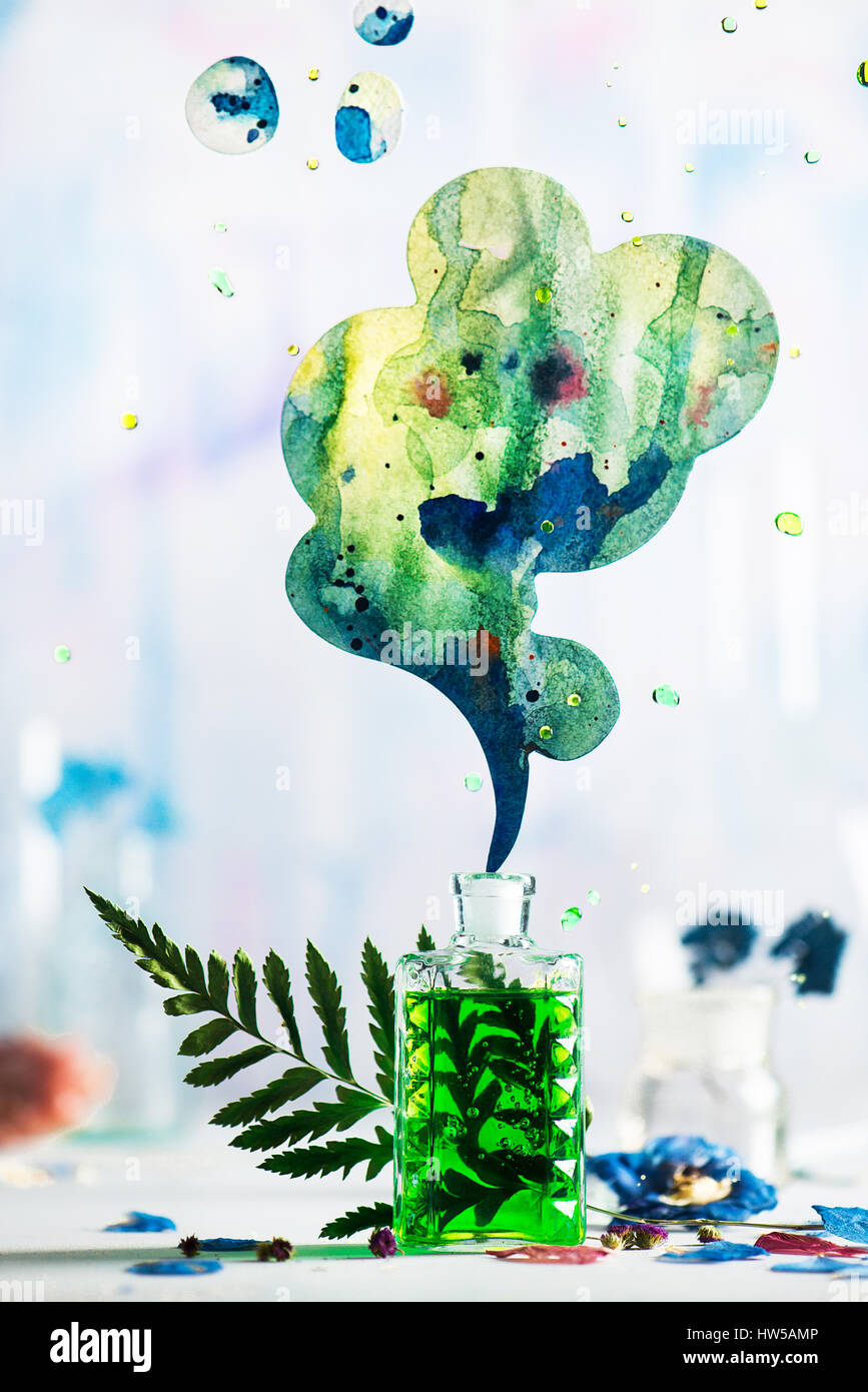 Glass perfume bottle with green liquid and a vibrant cloud of aroma on a white background - Stock Image