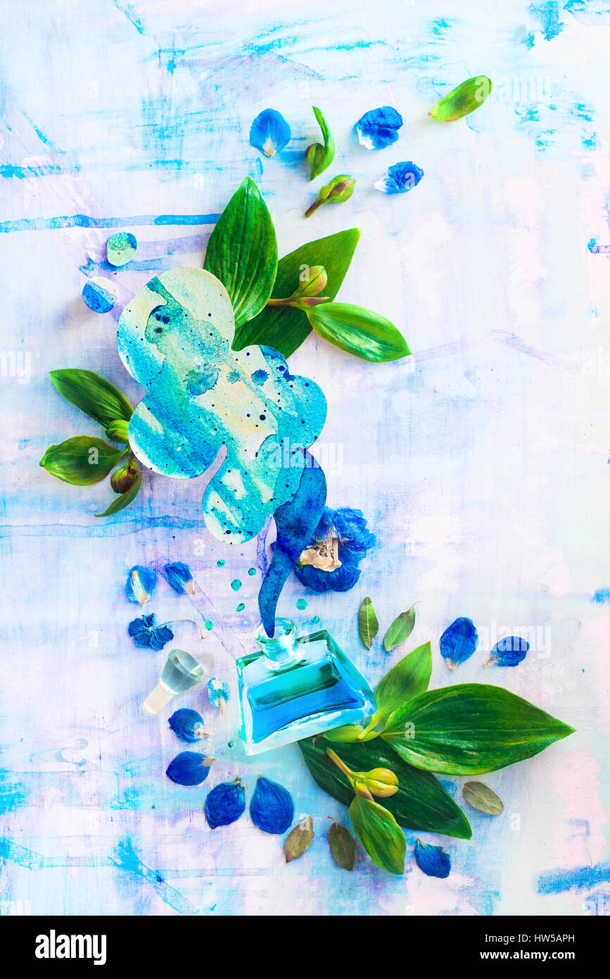 Glass perfume bottle with blue liquid, a cloud of aroma, flowers, petals and leaves on a light background - Stock Image