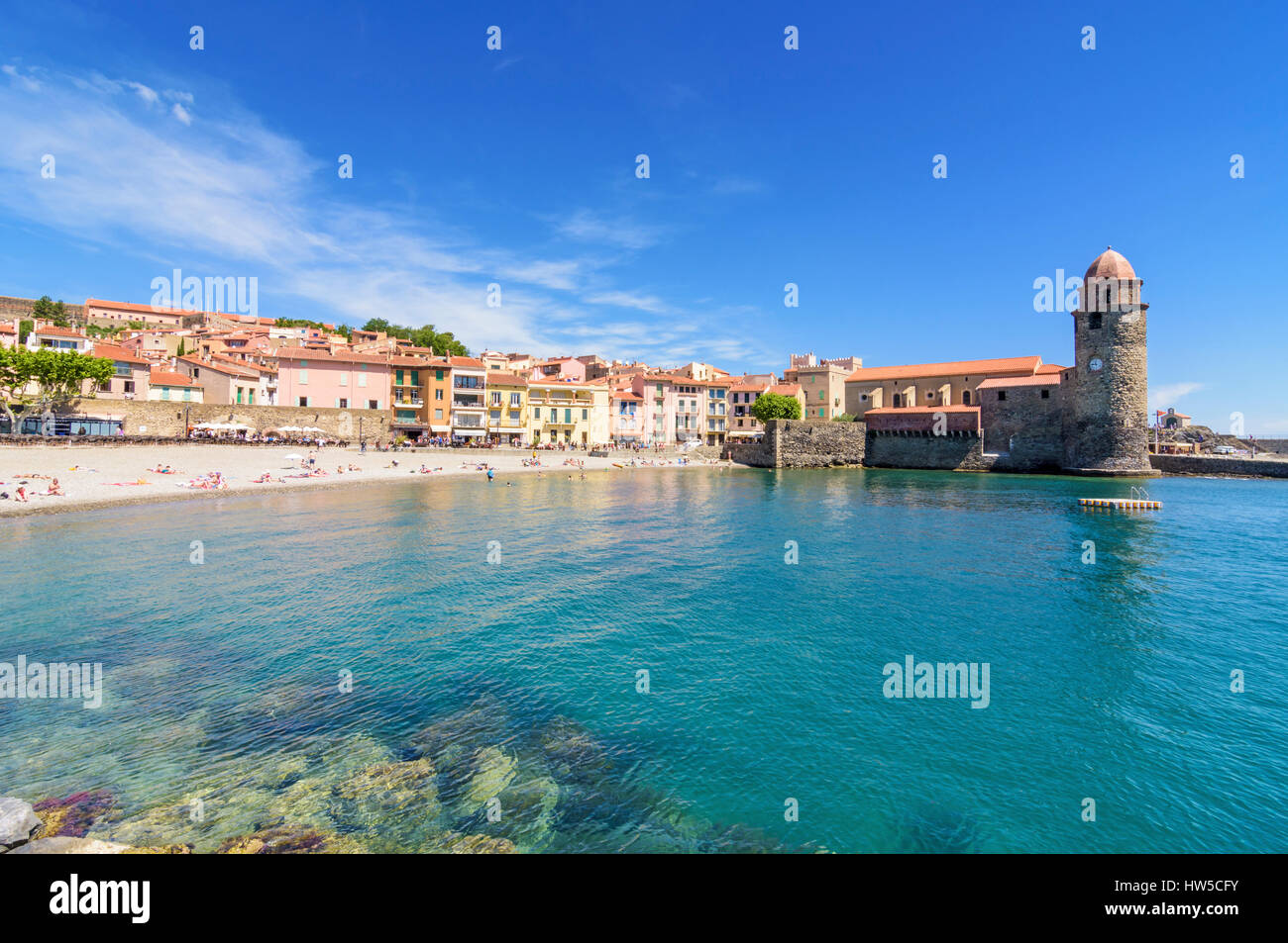 Collioure holidaymakers on Boramar Beach overlooked by the Notre Dame des Anges, Collioure, Côte Vermeille, - Stock Image