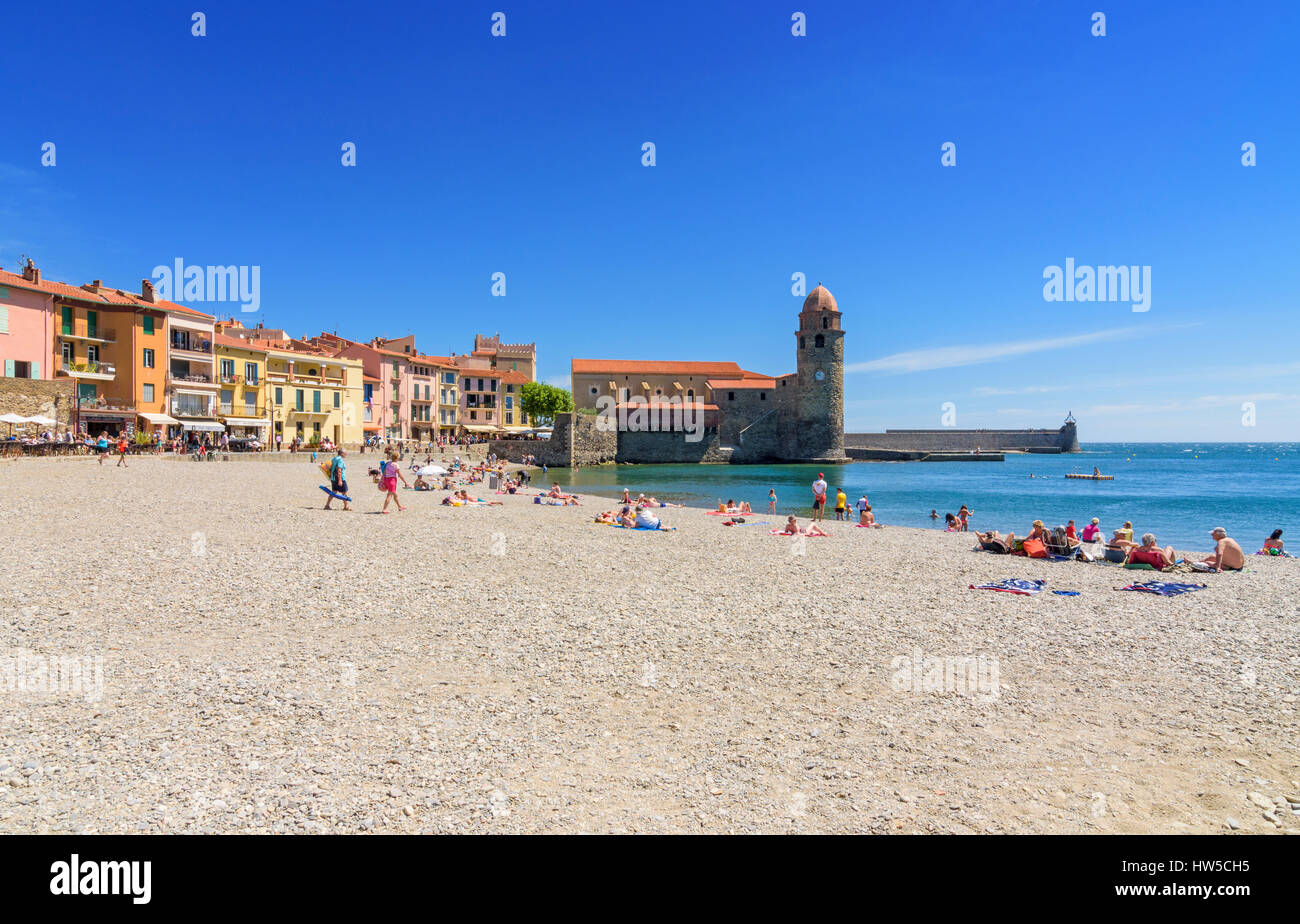 Holidaymakers on Boramar Beach overlooked by the Notre Dame des Anges, Collioure, Côte Vermeille, France - Stock Image
