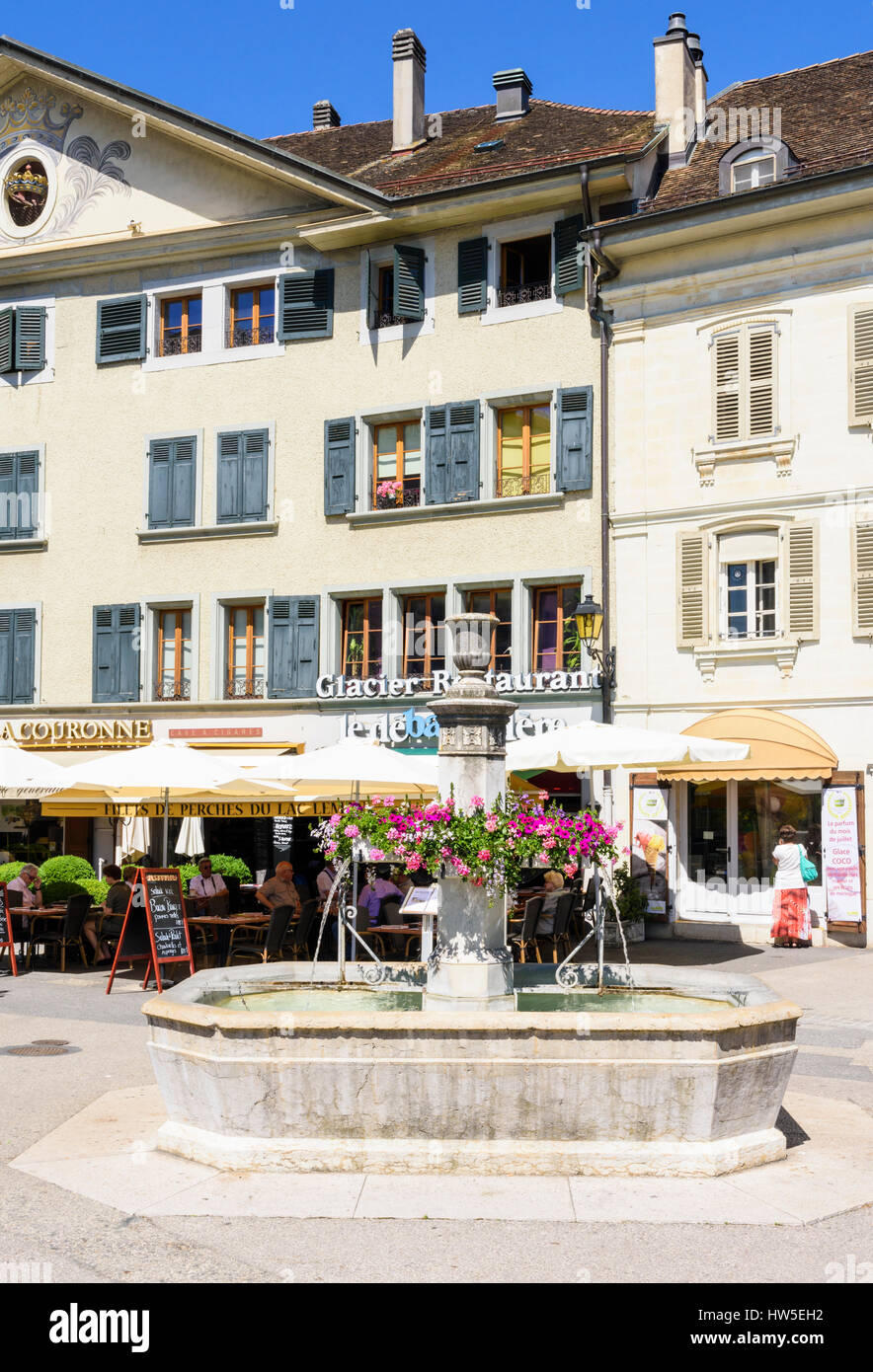 Cafes and restaurants behind a fountain in the old town of Nyon, Switzerland - Stock Image