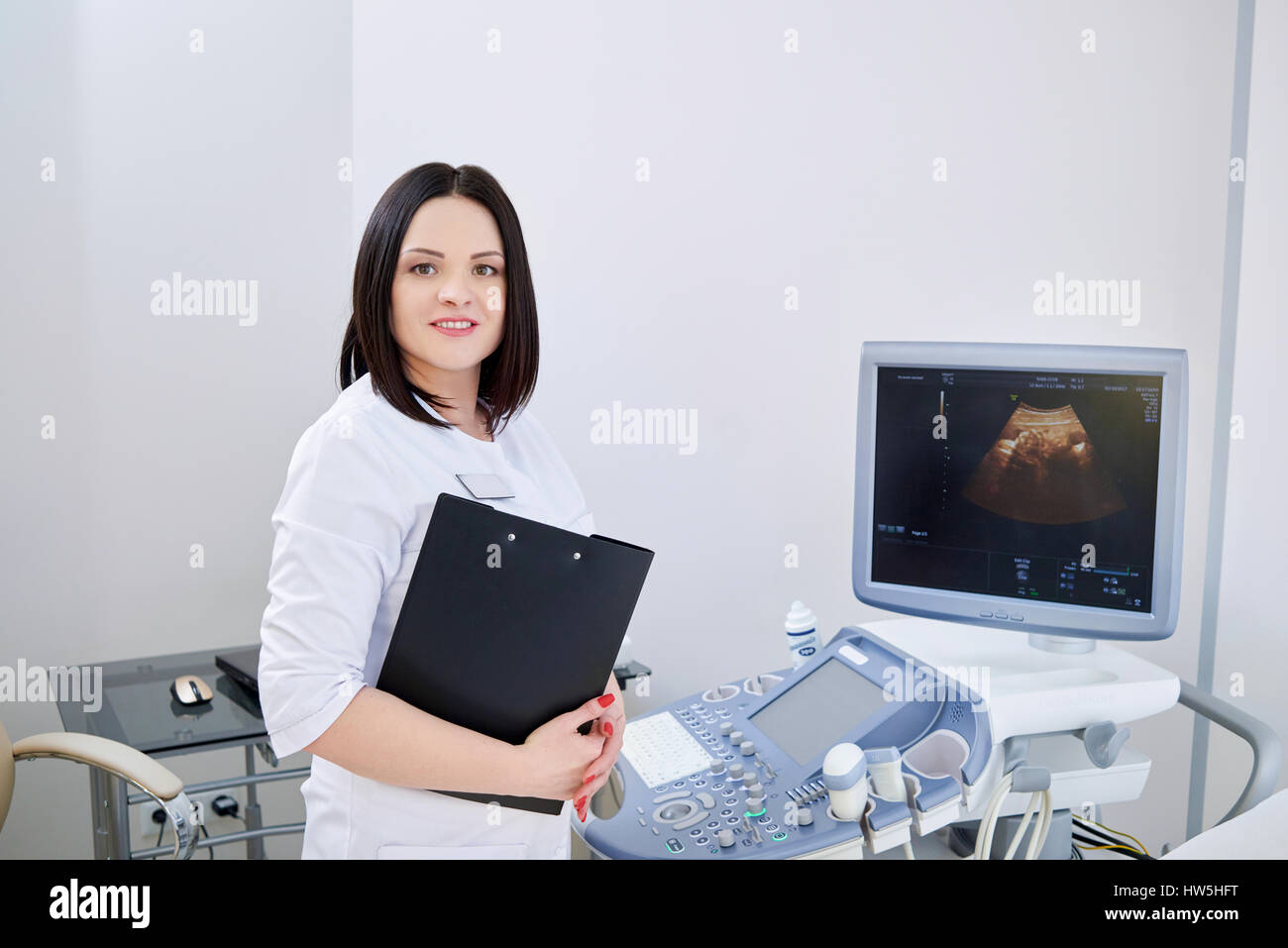 Cheerful female gynecologist posing at her office  - Stock Image