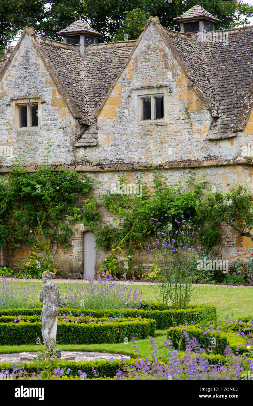 Garden statue and flowers at Lower Slaughter Manor House, Lower Slaughter, the Cotswolds, Gloucestershire, England, - Stock Image