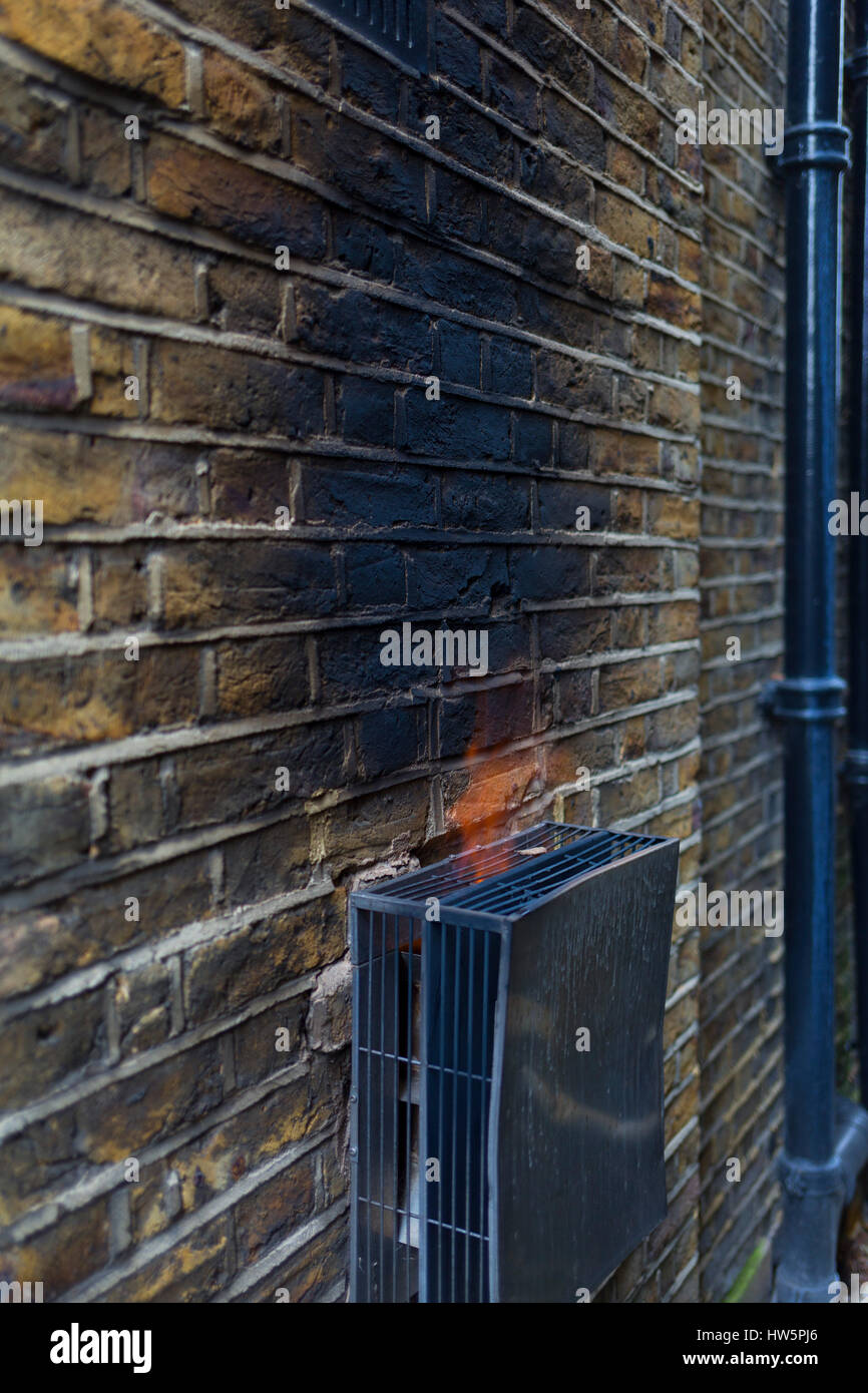 Flame emerging from a gas flue, with sooted and scorched brick wall of a house, blackened because of a faulty boiler, - Stock Image