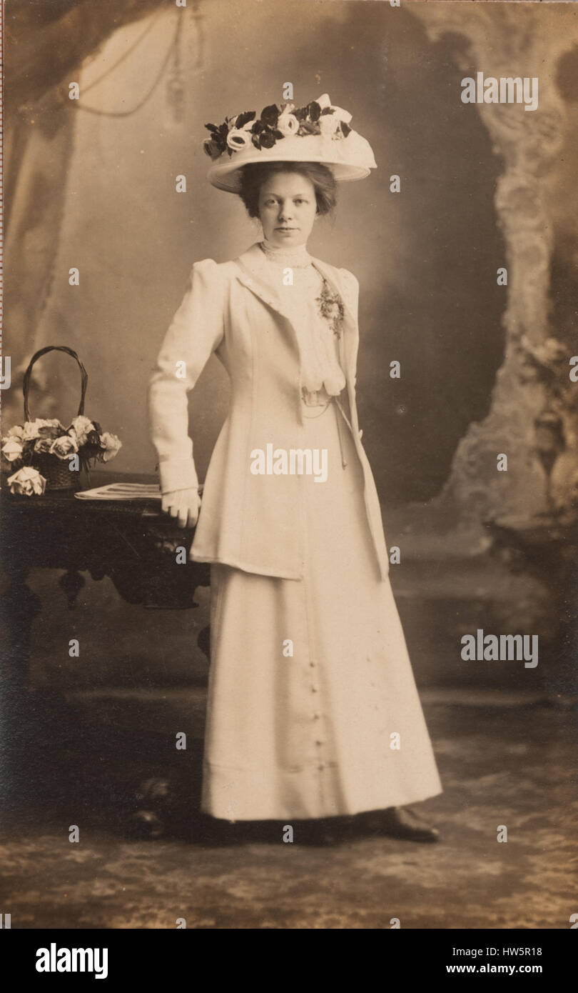 Vintage studio portrait,lady wearing a large hat with flowers on - Stock Image