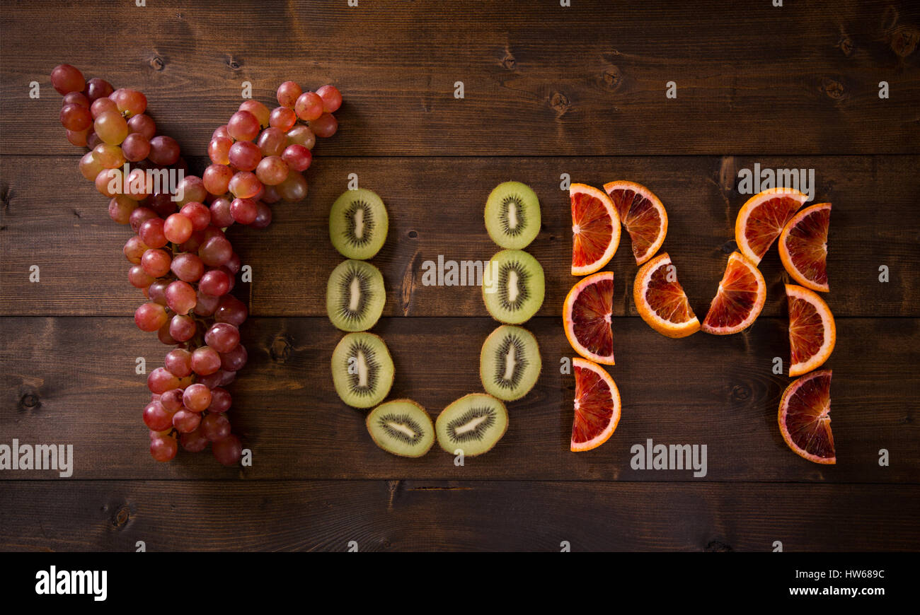 Fruit Spelling out YUM - Stock Image