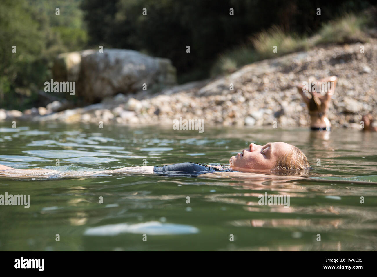 Girl floating in water - Stock Image