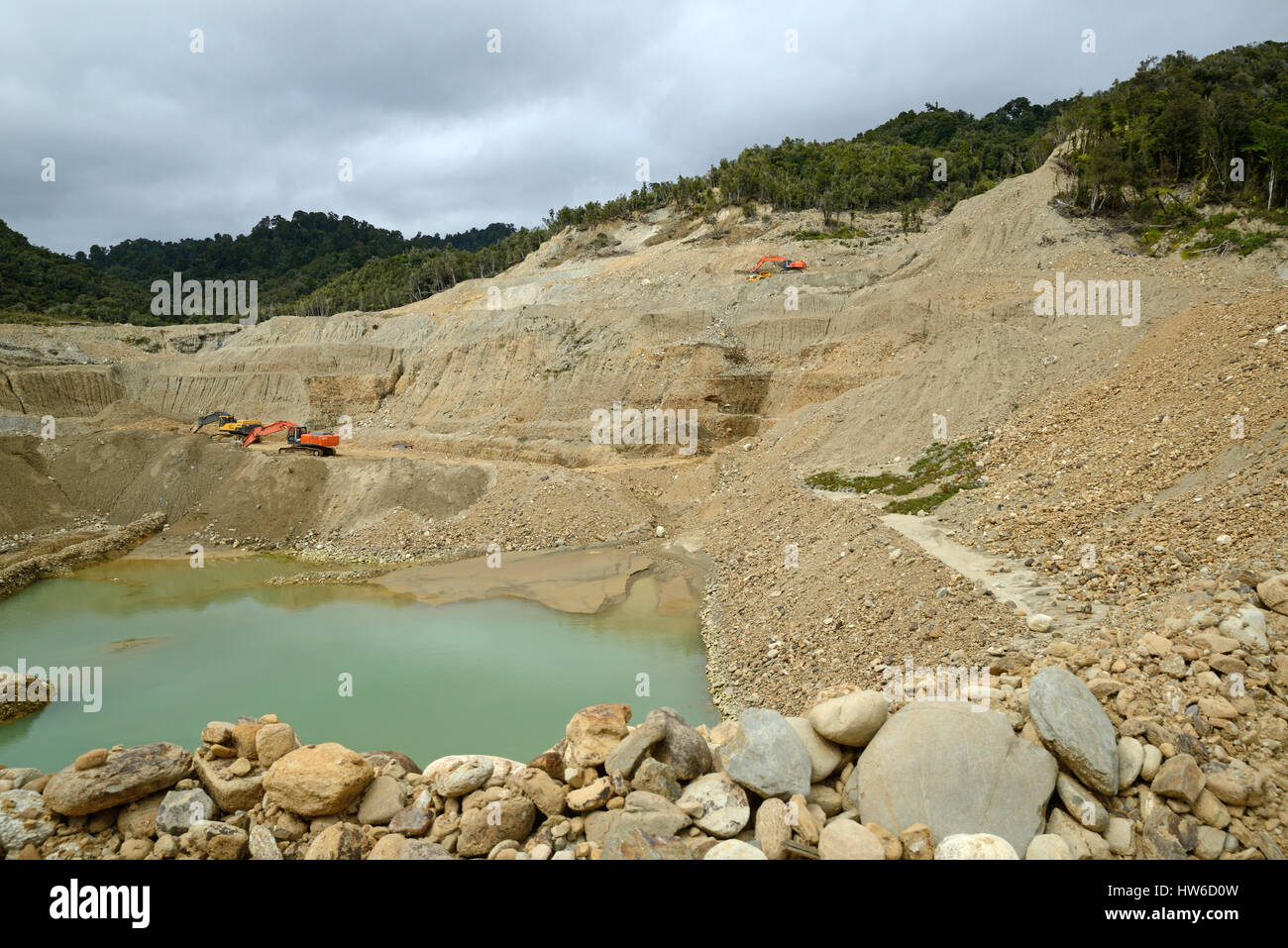 A digger clears overburden at an open cast mine to reach the gold-bearing paydirt below. Stock Photo