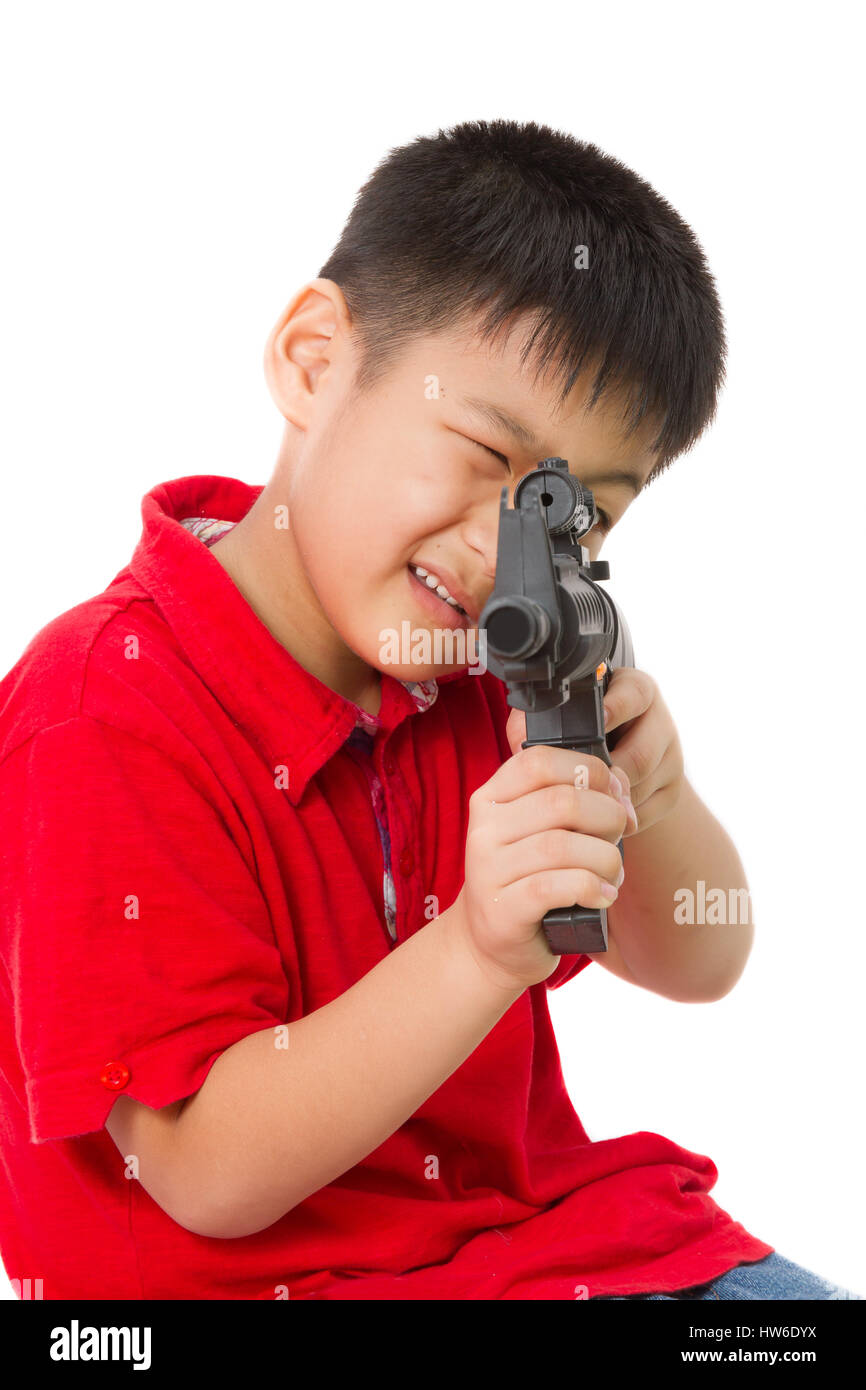 Asian Little Boy Playing Plastic Toy AK47 on White Background - Stock Image