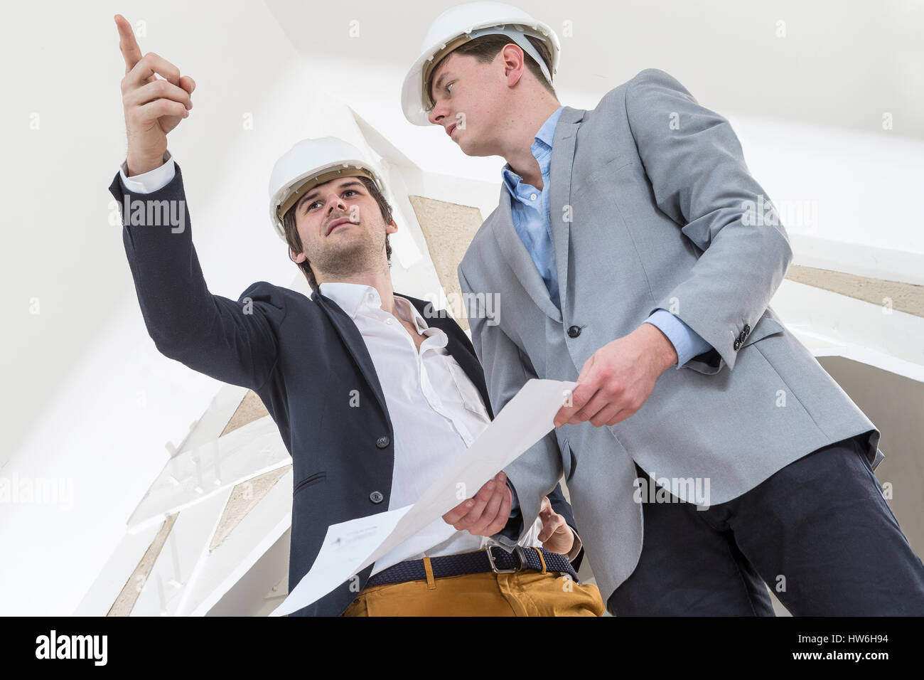 Two Engineer or Architect discuss on Project at Construction site in white envuronment - Stock Image