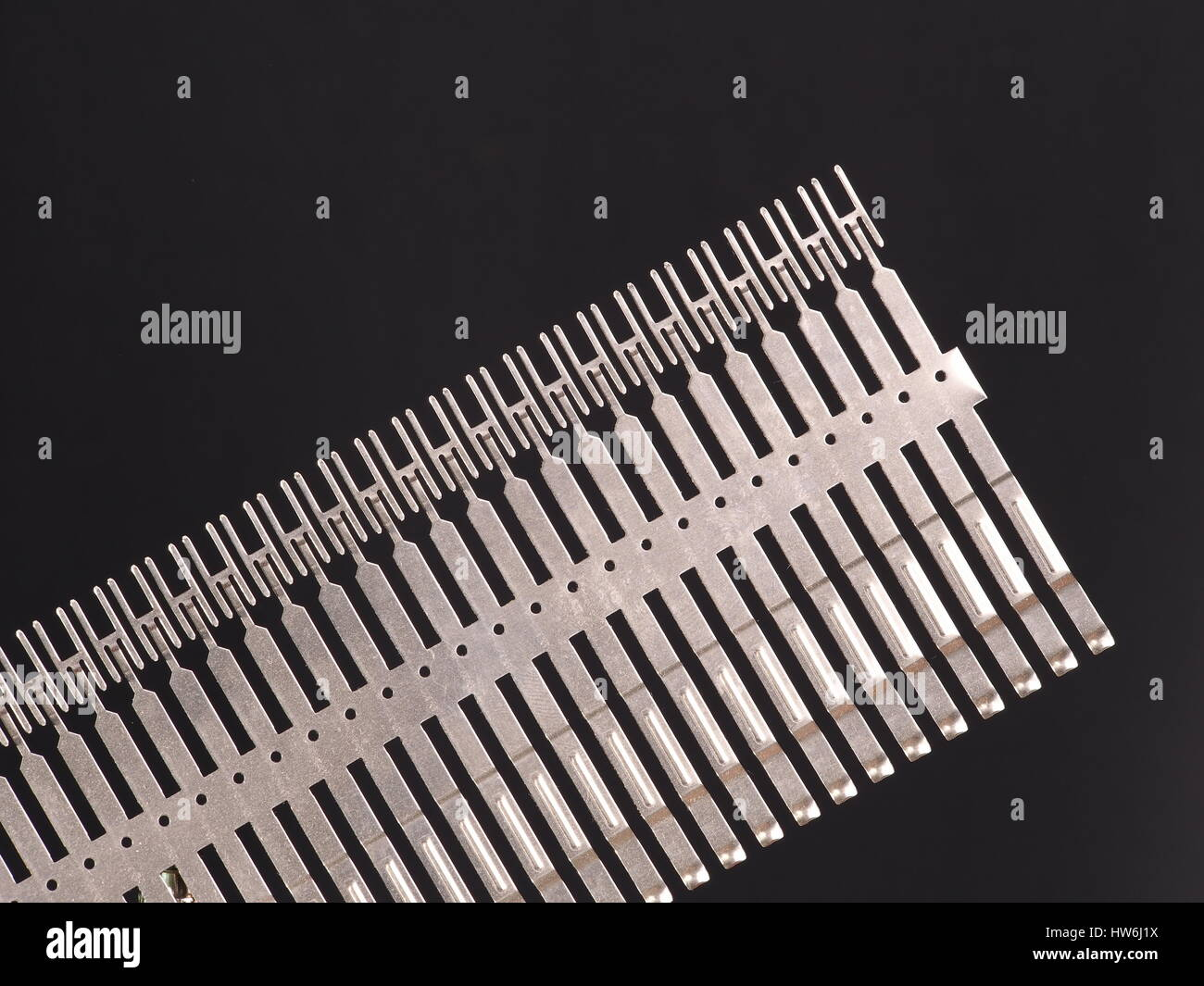 Stamped and plated row of precision springs on black background, Australia 2015 - Stock Image
