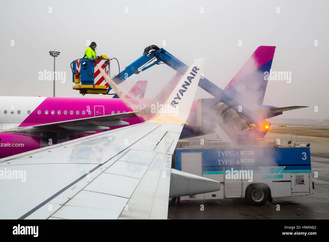 Clearing Ice And De-icing Aircraft. Budapest airport. Hungary, Southeast Europe - Stock Image