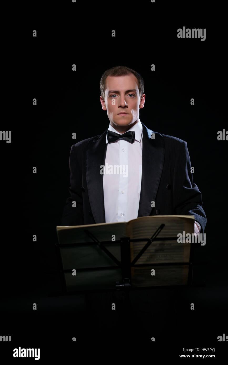 Orchestra conductor in black tuxedo in dark studio - Stock Image