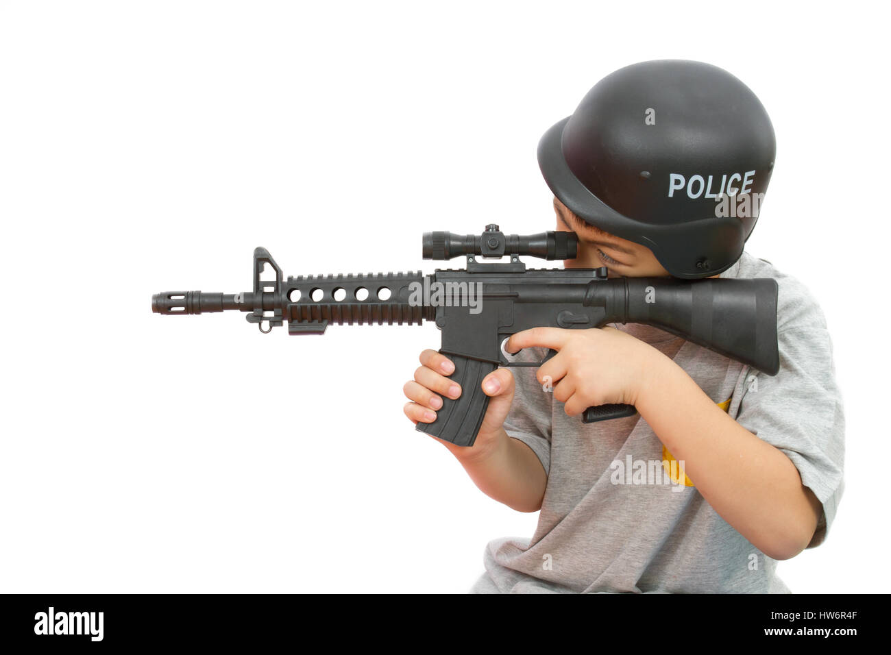 Asian Little Boy Playing Plastic Toy AK47 with Police Helmet on White Background - Stock Image