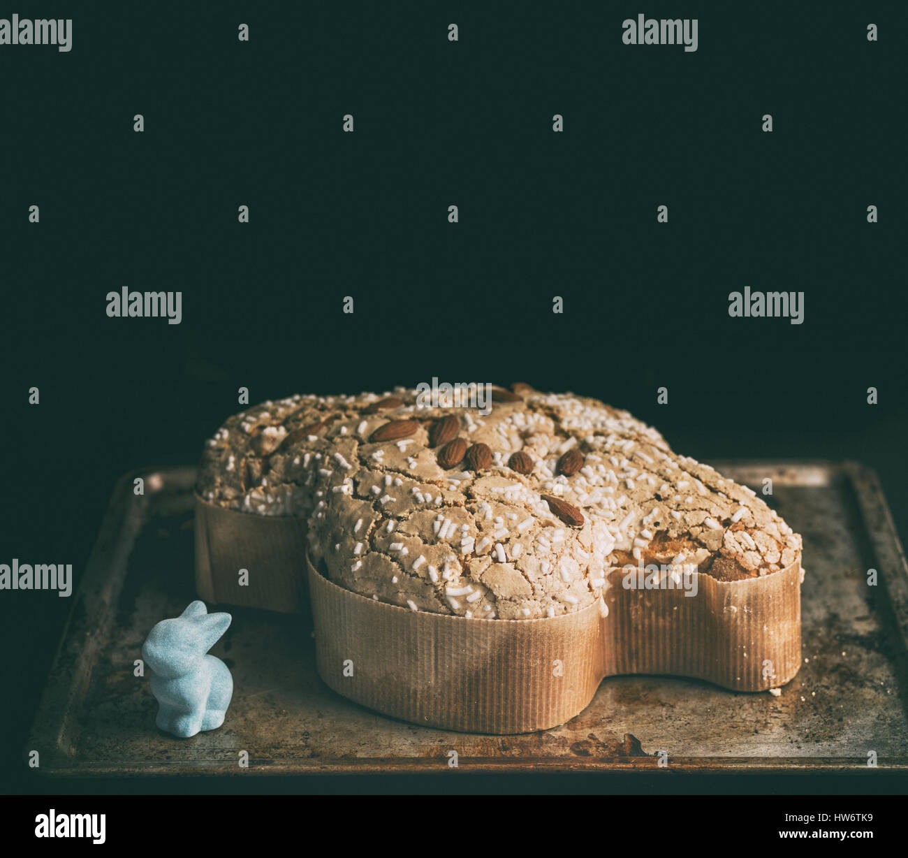 Colomba italian easter cake over a dark wooden table with some props - Stock Image