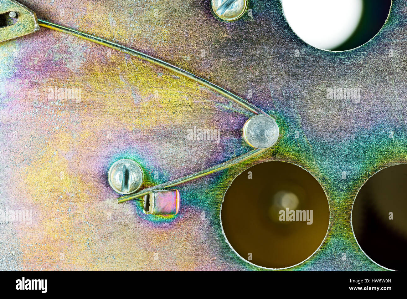 yellow galvanized zinc plate with compression spring, lever, screws - Stock Image