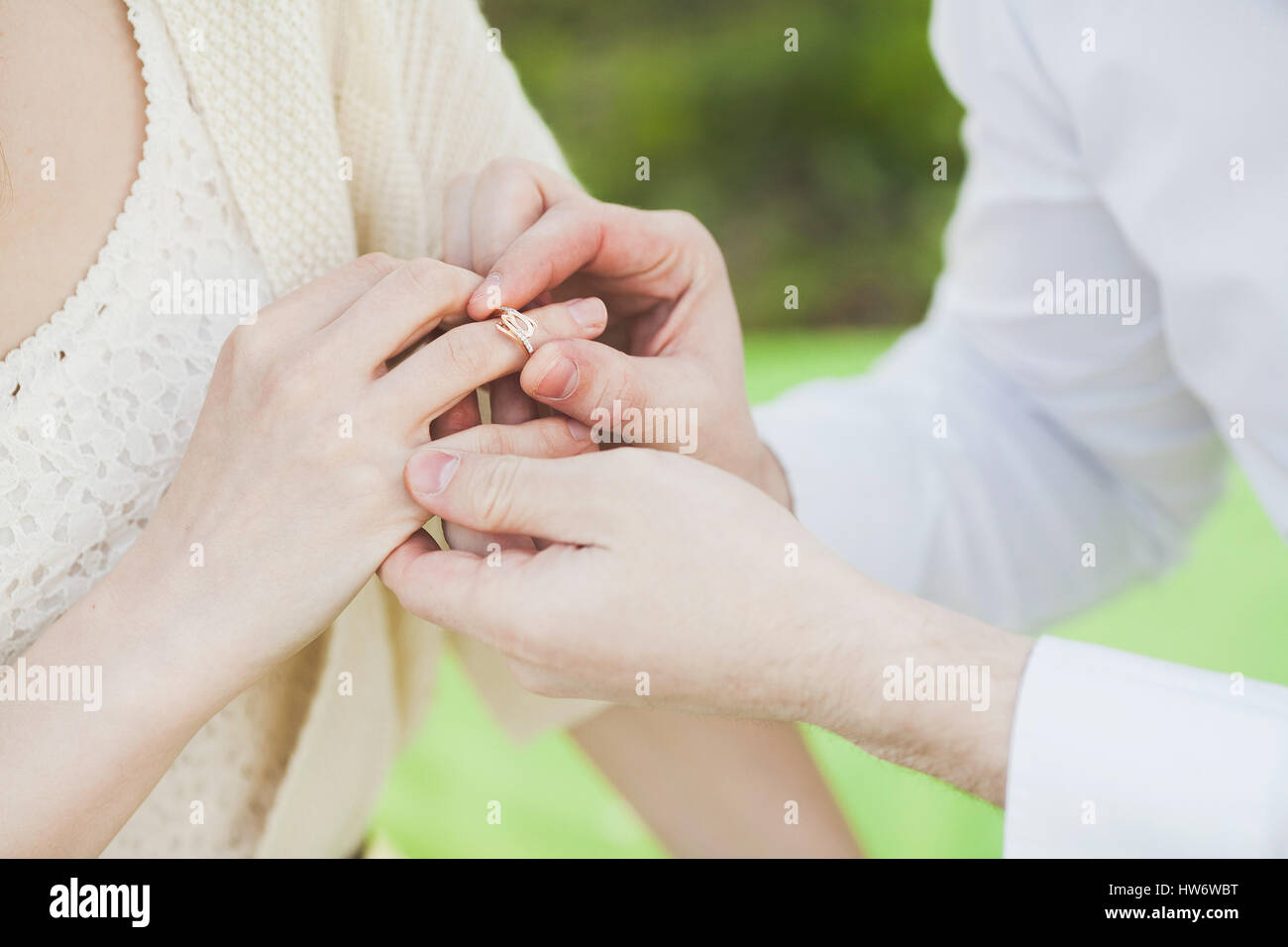 the offer to marry. hands of the man dressing a ring on the belo - Stock Image
