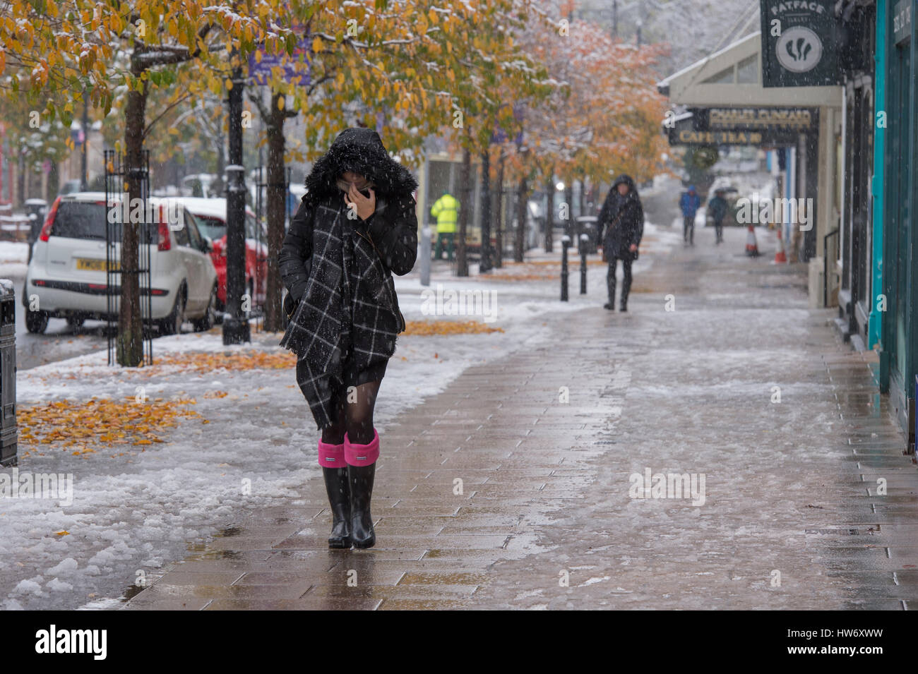 It is snowing and lady (other people too) wearing boots, scarf & winter coat with hood up, walks past shops on The Stock Photo