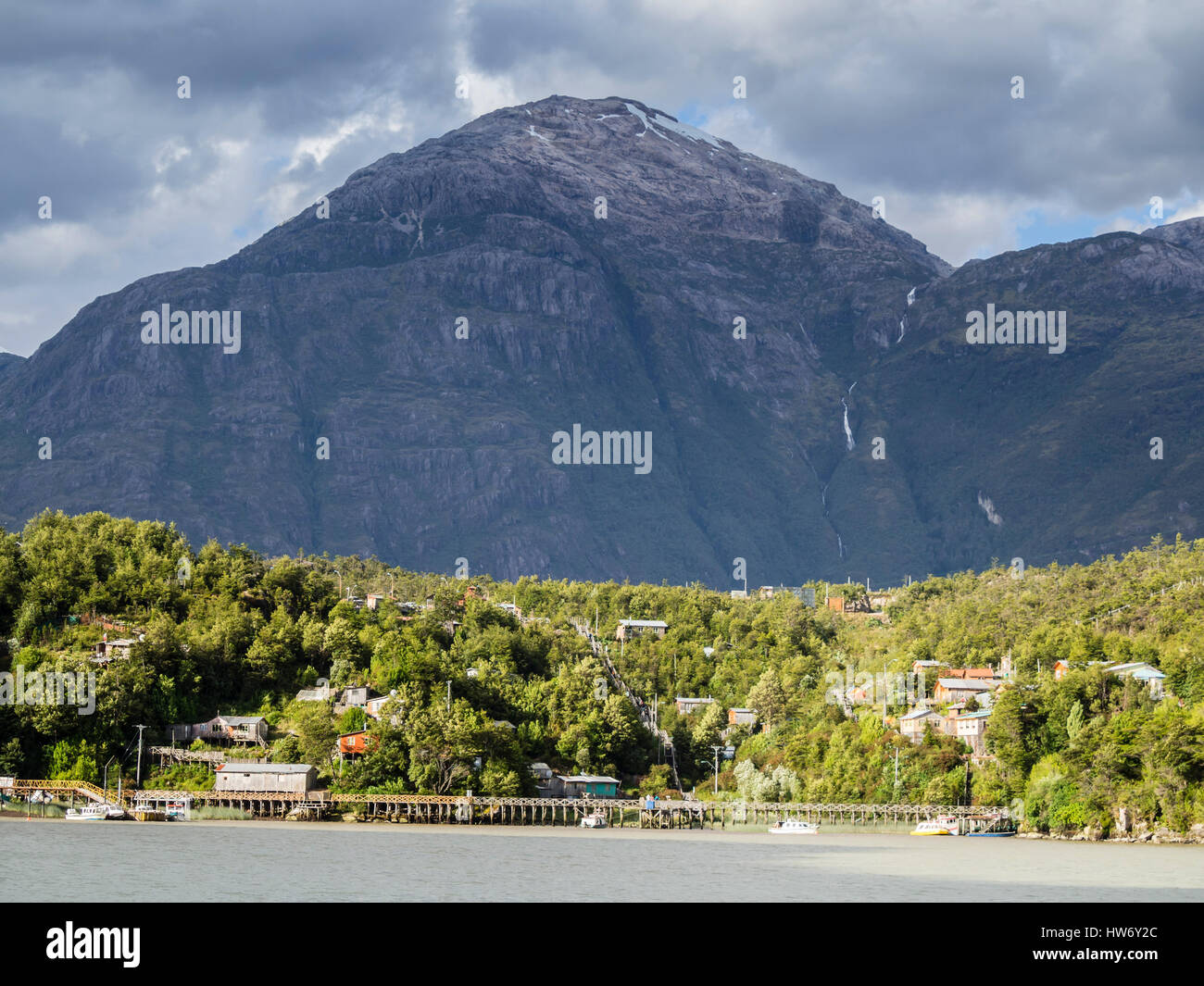 View over bay of Caleta Tortel against mountain range, houses and wooden boardwalk, Caleta Tortel,  Aysen region, - Stock Image