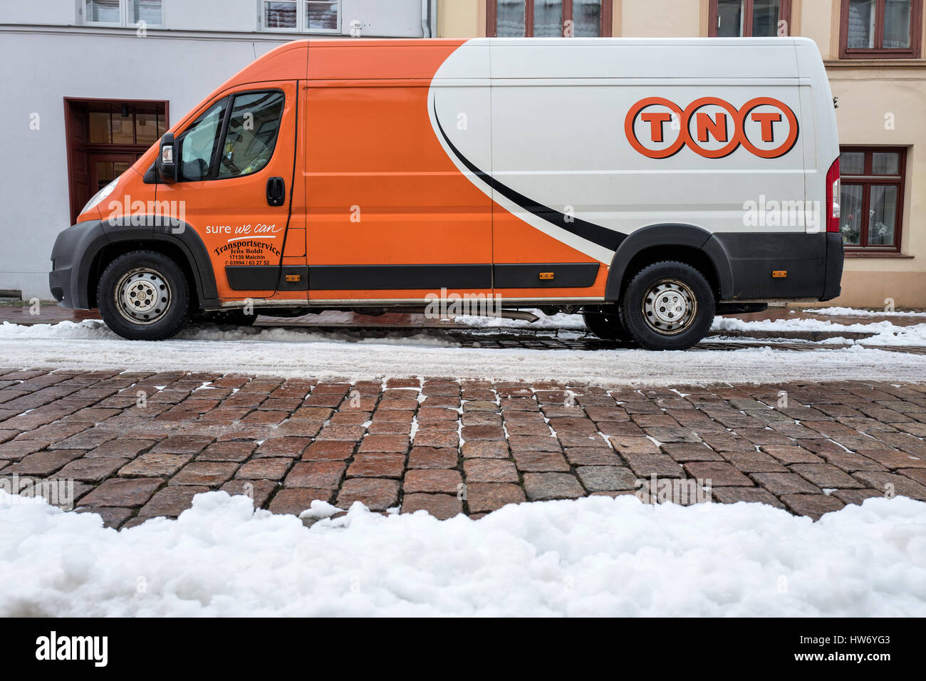 69f9b5a8c92fb6 TNT Express delivery van on a partly snow covered street - Stock Image