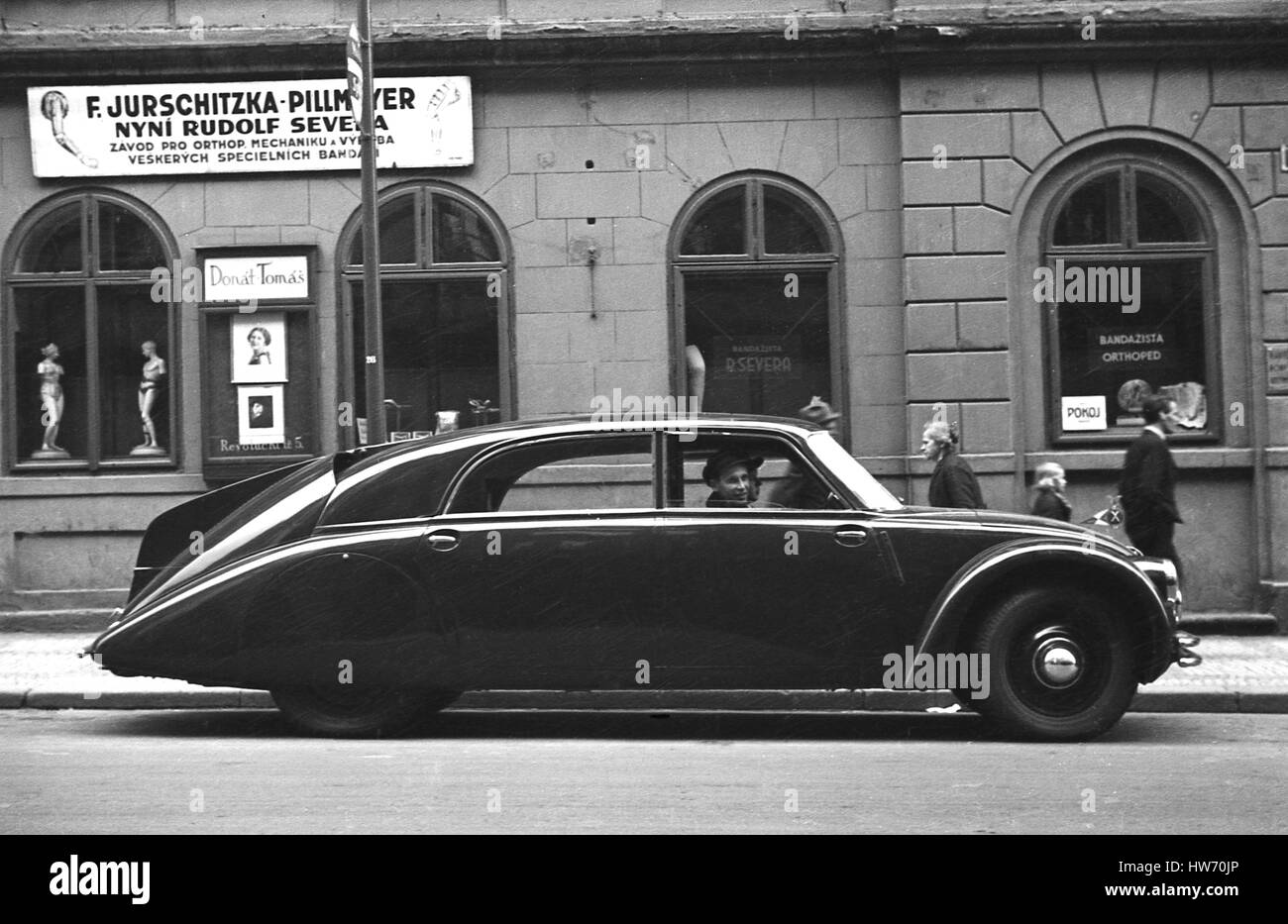1938, historical, a chauffeured driven Tatra 87 parked outside shops in Prague, Czechoslovakia. - Stock Image