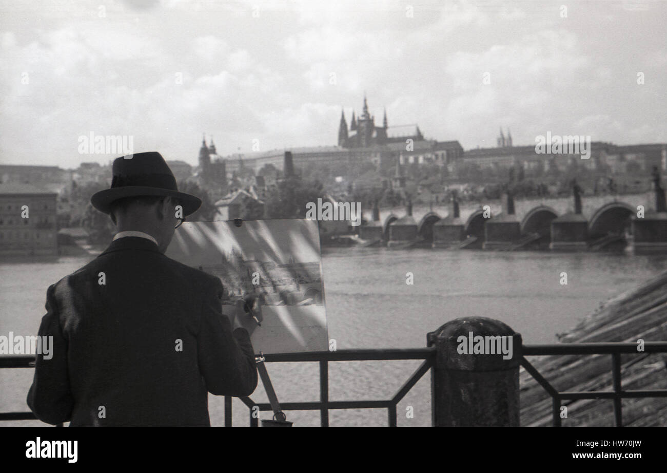 1930s, historical, male artist with hat painting a scene of Legion Bridge, over the river Vltava, Prague, Czecehoslovakia. - Stock Image