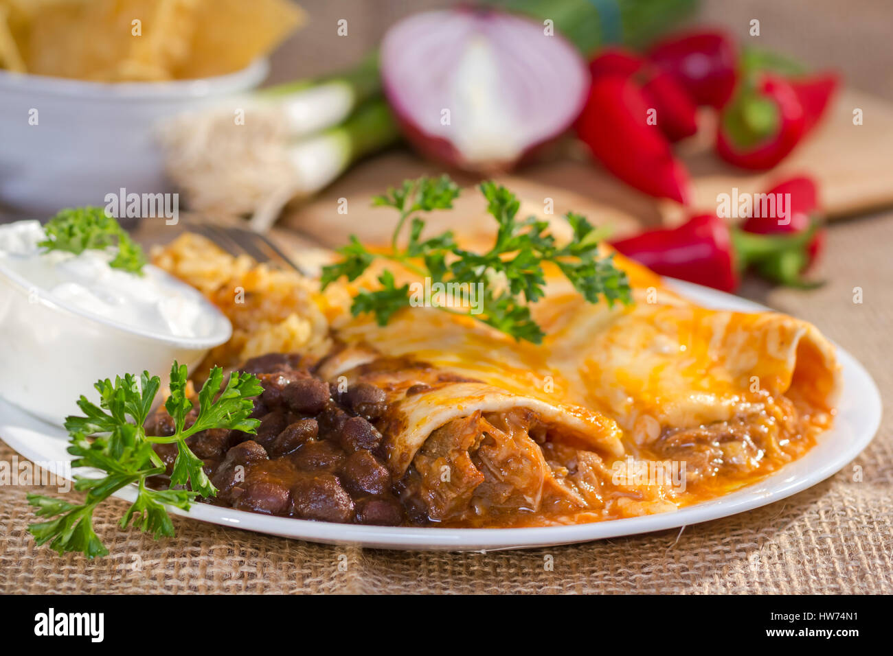 Southwest beef enchilada with sourcream and black beans. - Stock Image